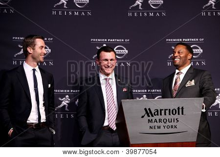 NEW YORK-DEC 8: Texas A&M offensive coach Kliff Kingsbury, quarterback Johnny Manziel & head coach Kevin Sumlin with 2012 Heisman trophy at the Marriott Marquis on December 8, 2012 in New York City.