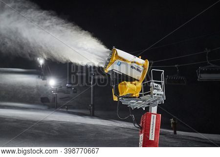 ALPE D'HUEZ, FRANCE - CIRCA 2020: Snow canon making artificial snow on a skiing slope at night. Snow guns are used more and more to extend skiing season due to global climate change and less snowfall