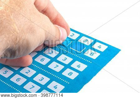 A Man's Hand Pastes A Sticker Into A Discount Magazine Of A Large Supermarket To Receive A Discount