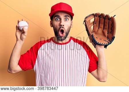 Young handsome man with beard playing baseball using ball and glove scared and amazed with open mouth for surprise, disbelief face