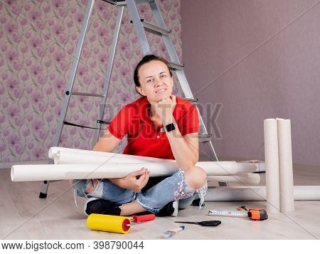 Renovation Of The Apartment. A Woman Renovation Of The Apartment. A Woman Is Sitting On The Floor Wi