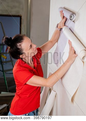 Repairs In The Room. A Woman Tries On Rolls Of Wallpaper On The Wall To Decide On The Choice Of Wall