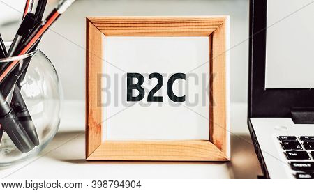 Abbreviation B2c - Short For Business To Consumer - In A Wooden Frame On A Table With A Laptop And P
