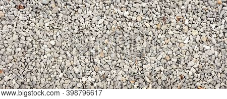 Small Stone Panorama Background. Dark Gravel Pebbles Texture. Grey Gravel Pattern