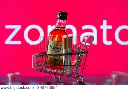 A Bottle Of Whiskey In A Trolley In Front Of A Zomato Board