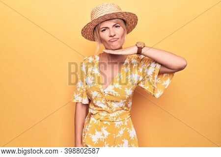 Beautiful blonde woman on vacation wearing summer hat and dress over yellow background cutting throat with hand as knife, threaten aggression with furious violence