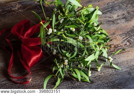 Branch Of Christmas Mistletoe With Red Bow On Wooden Table
