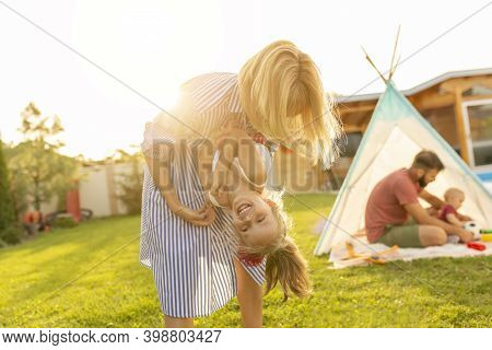 Happy Family Spending A Day Camping In Their Backyard, Parents Having Fun Playing With Children, Mot