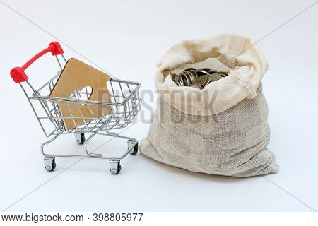 Mini-cart From A Supermarket, In Which There Is A House And An Open Bag With Money Next To It.concep