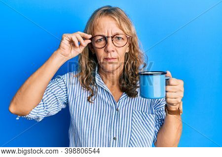 Middle age blonde woman wearing glasses and drinking a cup of coffee skeptic and nervous, frowning upset because of problem. negative person.