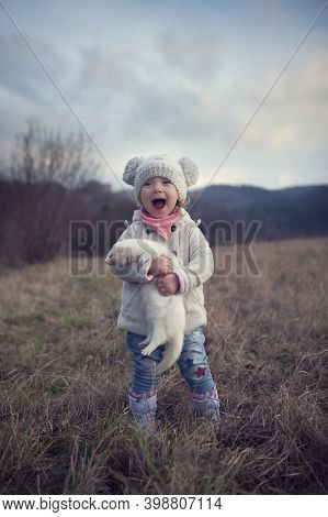 A Little Girl Is Outside With Her Pet. Cute Baby Girl Holding A Ferret In A Hand. The Child And His