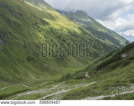 Green Summer Alpine Mountain Valley With Winding River Spring Stream And Tyrolean Walker At Stubai H