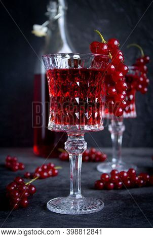 Glass With Red Currant Drink In The Foreground. A Bottle And A Glass With A Currant Drink In The Bac