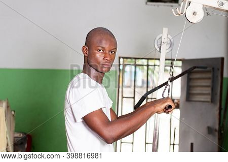 Young Man Doing Weight Training By Pulling A Weight By A Pulley.