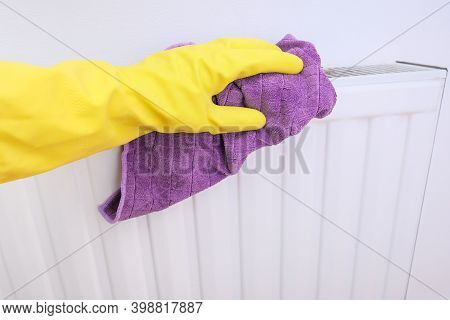 Radiator And House Cleaning, Hand In Yellow Rubber Gloves Wiping And Washing Central Heating Radiato
