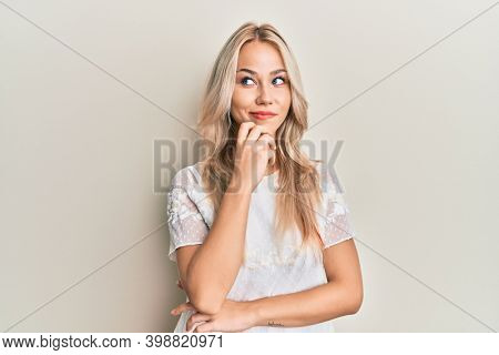 Beautiful caucasian blonde girl wearing white shirt thinking concentrated about doubt with finger on chin and looking up wondering
