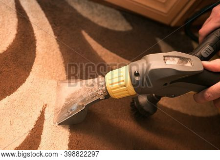 The Process Of Cleaning Carpets With A Steam Vacuum Cleaner. An Employee Of A Cleaning Company Clean