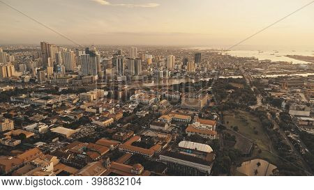 Sunset harbour city with ships, yachts at ocean bay aerial. Modern skyscrapers, cottages and houses at sun set light cityscape. Cinematic Philippines metropolis of Manila downtown drone shot