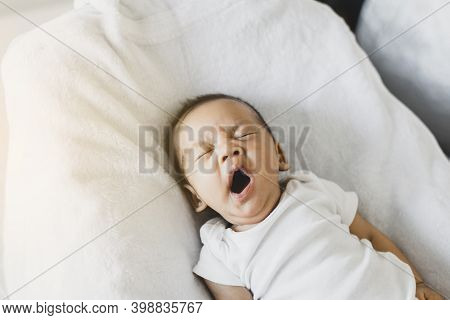 Lazy Newborn Baby Yawning Before Sleep On A Comfortable Bed At Home