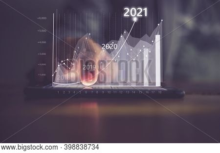 Augmented Reality (ar) Financial Charts Showing Growing Revenue In 2021 Floating Above Digital Scree