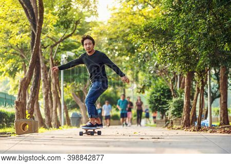 Asian Cheerful Man Playing Surfskate Or Skate Board In Outdoor Park When Sunrise Time Over Photo Blu