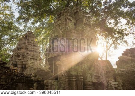 Ta Prohm Temple With Beautiful Sunbeam At Sunset. One Of Angkor's Best Visited Monuments In Siem Rea