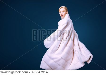 Fashionable model in an expensive white mink fur coat posing in motion on a dark blue background. Fur coat style.