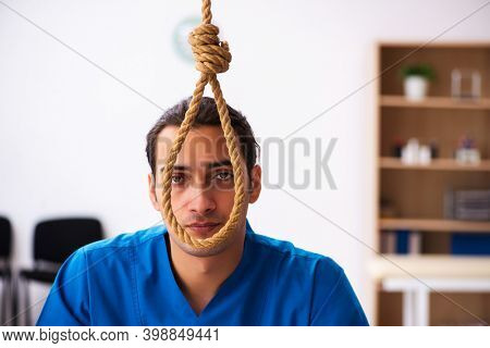 Young male doctor committing suicide at workplace