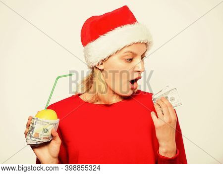 Richness Symbol Concept. Girl Santa Hat Drink Juice Lemon Wrapped Dollar Banknote. Rich Girl With Le