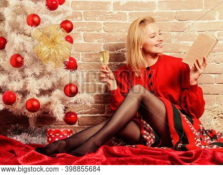Noel And Joy. Girl In Red Dress Relaxing With Glass Of Champagne Near Christmas Tree. Woman Happy Dr