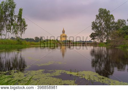 The Giant Golden Buddha With Reflection Of River Or Lake In Wat Muang In Ang Thong District With Pad