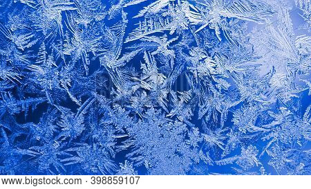 Ice Crystals Close-up On A Window Glass In Winter. Dark Blue And White Background Or Wallpaper. Myst