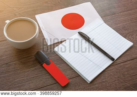 Japanese National Flag, Pen, Notebook, Marker And A Cup Of Coffee On A Wooden Table, Foreign Languag