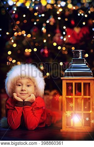 Happy little girl lying on a floor by a burning lantern and a Christmas tree at home. Merry Christmas and Happy new Year!
