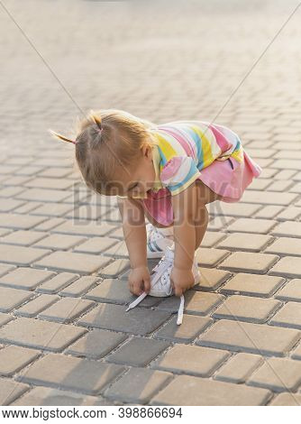 Fair-haired Baby In Tennis Clothes Ties Shoelaces At Sunset