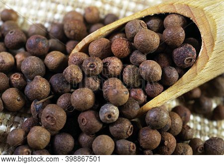 Allspice In A Wooden Scoop On The Table Close Up. Selective Focus