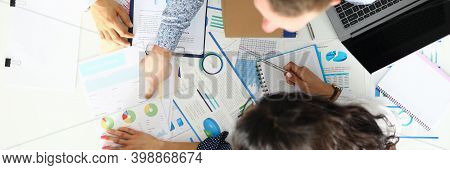 Man Shows His Colleagues Diagram On Documents On Work Desk In Office Closeup. Implementation Of Busi