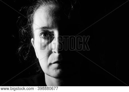Dark Portrait Of A Serious Woman With Only Half Her Face Lit Up On A Black Background Looking Sad Or