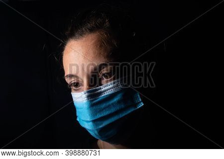 Close-up Of A Dark Portrait Of A Very Dimly Lit Woman. The Woman Is Wearing A Surgical Mask, Her Gaz