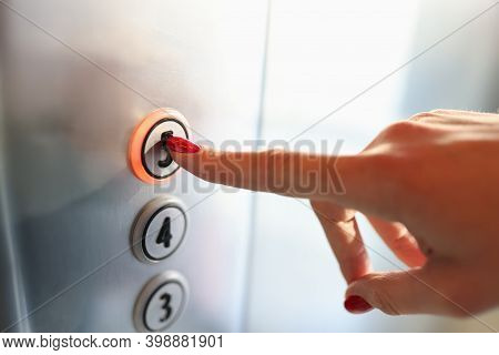 Womans Hand Pressing Button Of Elevator To Fifth Floor Close-up. Repair And Maintenance Of Elevators