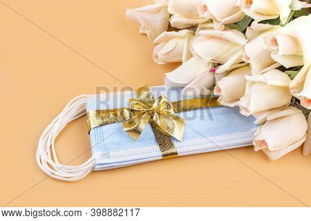 A Bouquet Of Roses And Protective Medical Masks With A Golden Ribbon And Bow On A Pastel Background.
