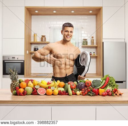 Variety of fruits and vegetables on a wooden counter and a topless man with a mesuring scale in a kitchen