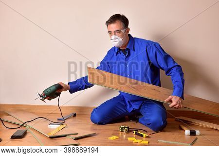 Professional Parquet Assembler With Cutting Machine In Hand Sitting On The Floor Assembling Parquet.
