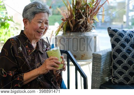 Old Asian Elderly Senior Elder Woman Drinking Avocado Smoothie Yogurt Milkshake At Restaurant. Matur