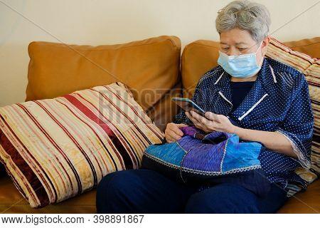 Asian Elder Senior Woman Elderly Wearing Facial Mask Using Mobile Smart Phone Cellphone. Mature Reti