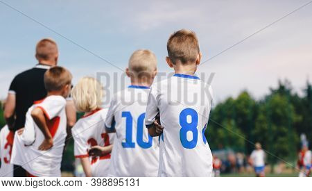 Boys In Soccer Jersey Shirts With Numbers On Its Back. Coach Of Children Sports Team On A Sideline.