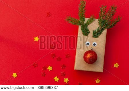Creative Christmas Gift Box In The Form Of A Deer Against A Red Background. Holiday Greeting Card.
