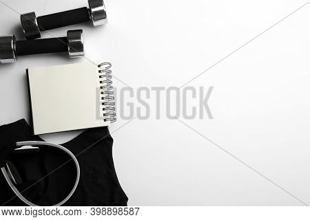 Flat Lay Composition With Sportswear, Notebook And Dumbbells On White Background, Space For Text. Gy