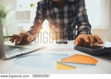 People Planning And Analysis With Financial Graph Paper Document And Check In Laptop Working On Tabl