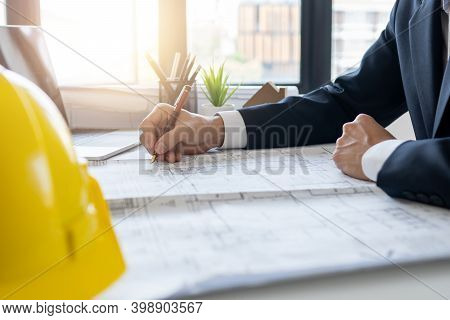 Architect Drawing And Make Construction Plan On Blueprint In Office